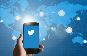 Image of mobile phone showing Twitter icon and map of the world