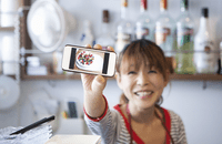 Image of cafe owner with video on phone screen