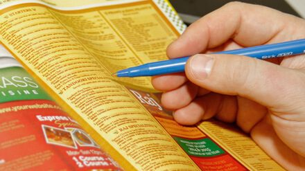 Hand holding pen while viewing Yellow Pages restaurant's page