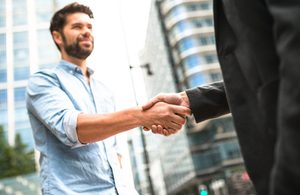 Human versus corporate - business handshake