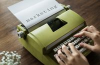 "Green typewriter with the word ""marketing"" typed in a bold font."