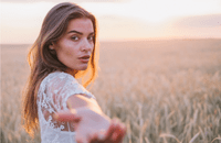 A girl in a corn field, holding out her hand