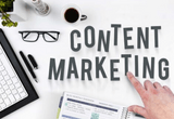 """A desk """"flatlay"""" with a hand pointing to the words """"content marketing""""."""