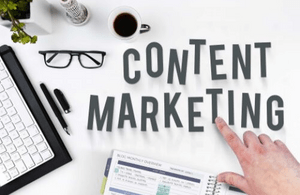 "A desk ""flatlay"" with a hand pointing to the words ""content marketing""."
