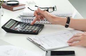 person performing calculations on a calculator on a table with notepads and glasses