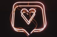 neon pink sign of a heart inside a speech bubble