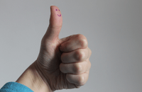 Thumbs up with a smiley face drawn on the thumb.